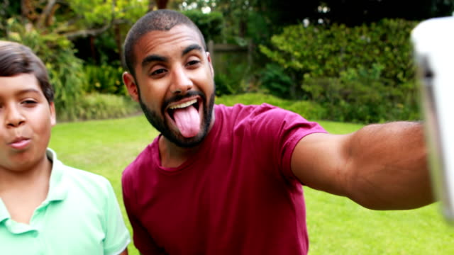Father and son taking selfie with mobile phone 4k video