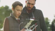 Father and Son Using Remote Control for Drone in the Park. video