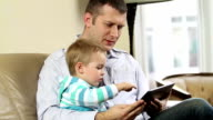 Father and son using wireless tablet video