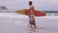 Father and son walking with surfboard. video