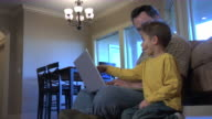 Father and son with laptop computer video