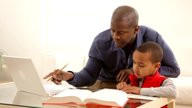 Father and son working on homework together video