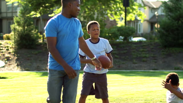 Father and sons play football video