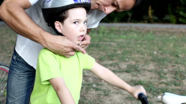 Father Assisting Child With Cycling Helmet. video