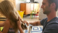 Father Brushes Daughter's Hair As She Sits At Table video