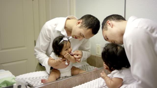 Father brushing babies teeth video