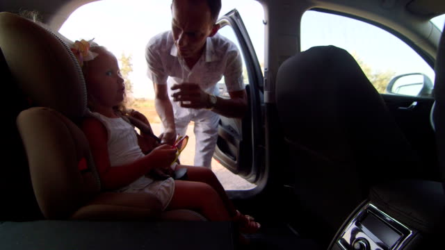 Father carrying his little daughter by car in child safety booster seat video