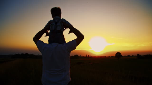Father carrying his son on shoulders video