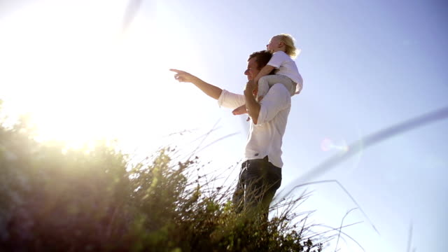 Father carrying son on shoulders in the dunes video