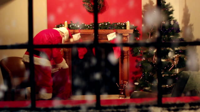 Father Christmas delivering presents through window video