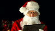 Father Christmas, Santa Claus in sleigh on Tablet, close video