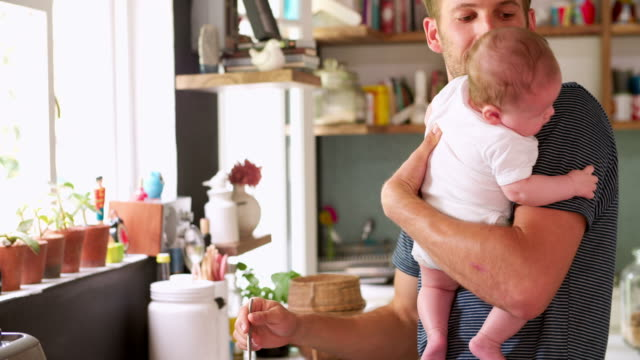 Father Cooking Meal Whilst Holding Baby In Kitchen video