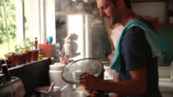 Father Cooking Meal Whilst Holding Daughter In Kitchen video