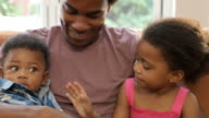 Father Cuddling Baby Son And Daughter On Sofa At Home video