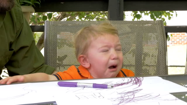A father hands a marker to his crying frustrated young child boy in slow motion video