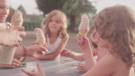 A father hands out ice cream cones to his kids at a picnic table video
