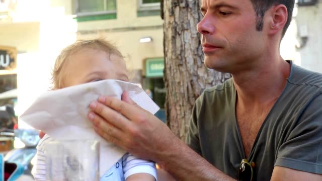 Father helping baby clean snot from nose. Dad removing mucus from toddler baby video