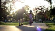 Father Helping Young Daughter Ride Her Bike video