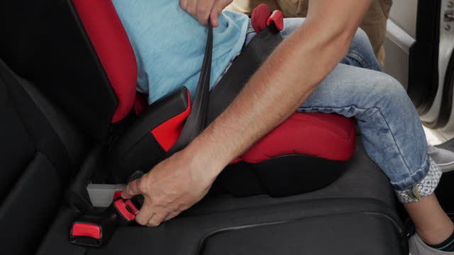 Father helps his son to fasten belt on car seat while his son is sleeping video