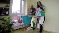 Father hold newborn baby child and mother pick laundry. video