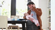 Father holding baby working from home on phone video