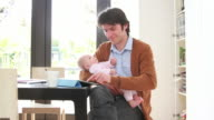 Father holding baby working from home video