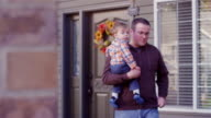 A father holding his baby boy and walking in front of their house video
