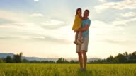 SLO MO DS Father holding his little daughter in the sunny meadow video