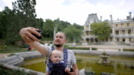 Father holding his young son and makes selfie phone. They travel together video