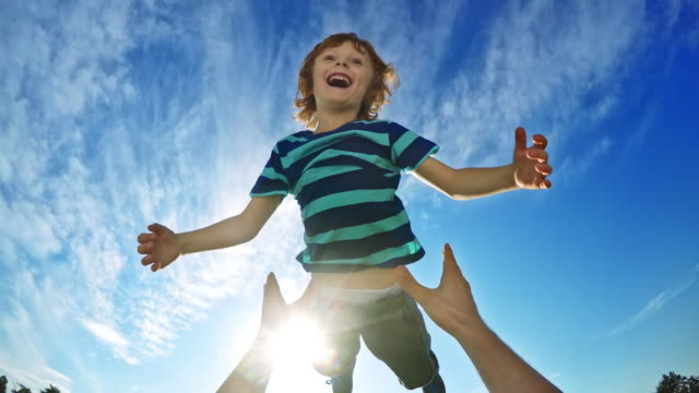 POV Father lifting his laughing son into the air on a sunny day video