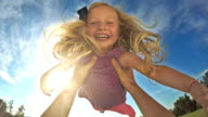 POV Father lifting his smiling daughter into the air on sunny day video