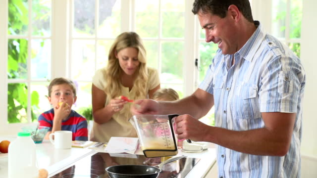 Father Making Scrambled Eggs For Family Breakfast In Kitchen video