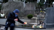 Father man put candle on daughter son grave in graveyard. video