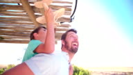 Father piggybacking his son playing with a toy wooden plane video