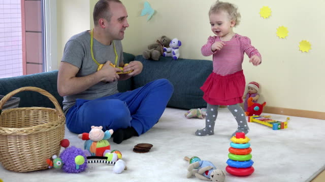 father play with toy guitar and cute baby daughter dancing. FullHD video