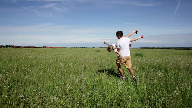father playing with his daughter in field video