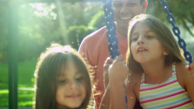 Father pushes daughters on a tire swing video
