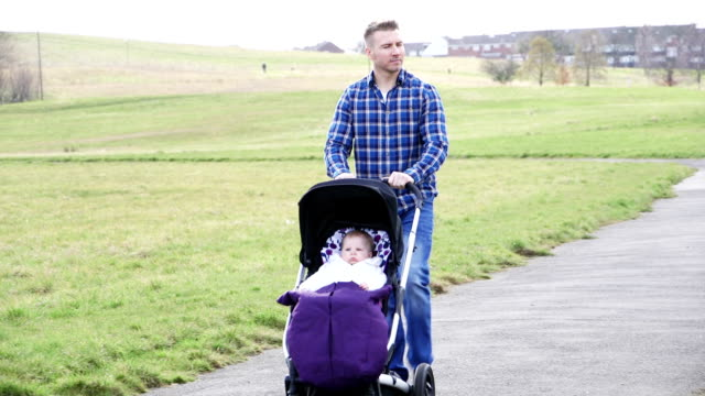 Father pushing baby stroller video