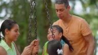 'Father pushing his daughters on a tire swing in a park ' video