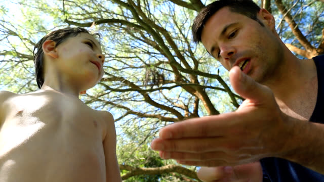 Father putting suncreen to his 6-8 year old child. Parent putting lotion to his kid video