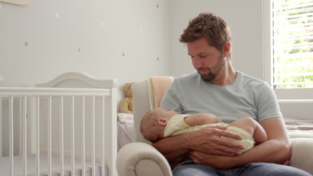 Father Sitting In Nursery Chair Holds Sleeping Baby Son video