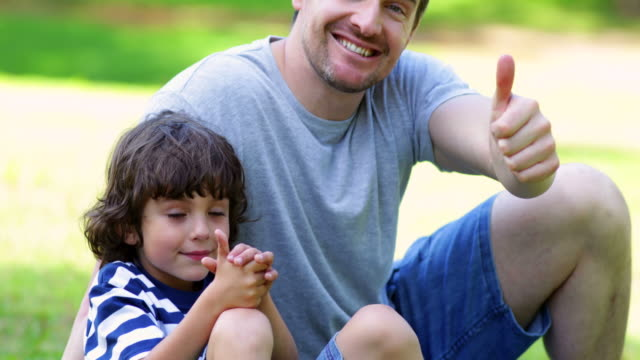 Father sitting with son in park showing thumbs up video