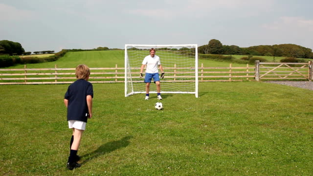 Father & Son playing soccer / football video