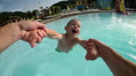 SLOW MOTION POV: Father spinning happy little boy in sunny summer video