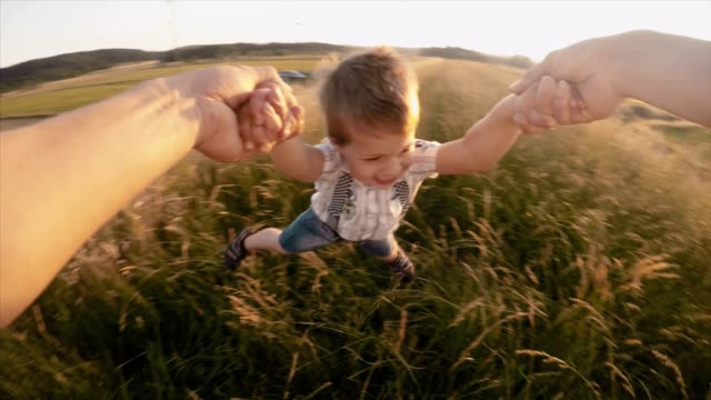 SLO MO POV Father spinning his cute son in grass video