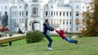 Father, spinning in circles his little son on a lawn in front of the Hluboka castle in Czech Republic video