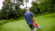 A father spins his 5 year old son around in circles on the grass - slowmo video
