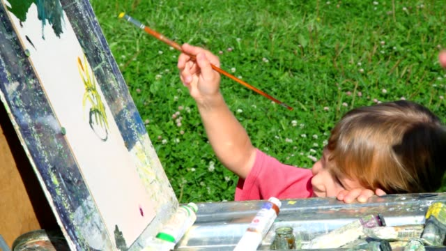 Father teaching his little daughter to painting by oil paint video