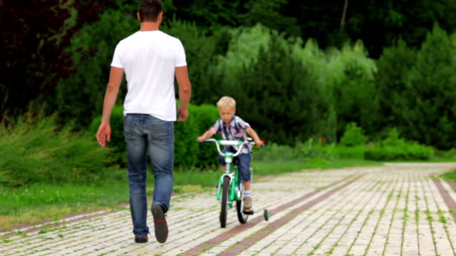 Father teaching his son to ride a bike video