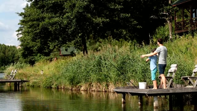 Father teaching son to fish at freshwater pond video